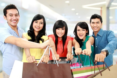 Group of people holding many shopping bags shopping together isolated on white background photo