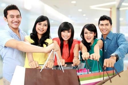 filles shopping: Groupe de personnes d�tenant des sacs nombreux commerces parcourez ensemble isol� sur fond blanc
