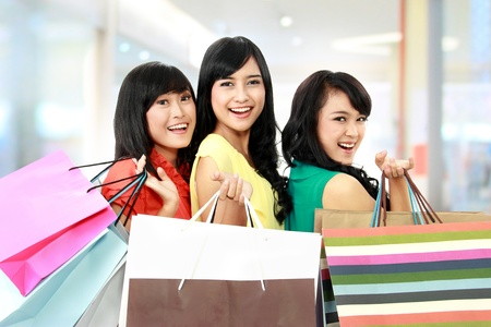 malls: asian woman shopping with friends together isolated on white background