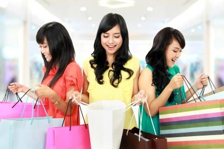 filles shopping: Portrait d'une femme heureuse d'achats regarder � l'int�rieur des sacs au centre commercial