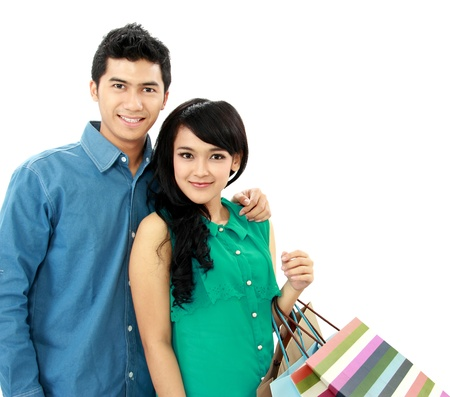 Romantic young couple shopping and holding many shopping bags isolated on white background photo