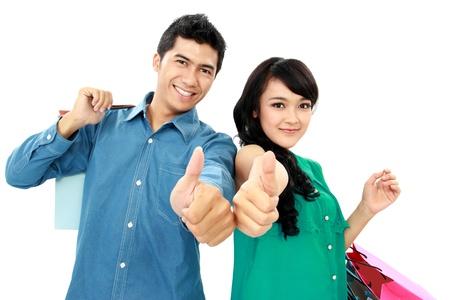pulgar levantado: Joven pareja rom�ntica que muestra el pulgar hacia arriba mientras sostiene muchos bolsos de compras Foto de archivo