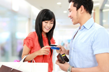 credit card purchase: portrait of young man pay using credit card while shopping Stock Photo
