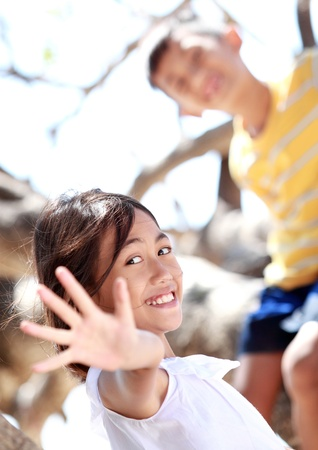 people laughing: Two little boy and girl playing on the tree Stock Photo