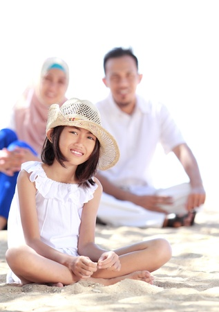 muslim baby: Portrait of young little girl in the beach smiling with her parent as background