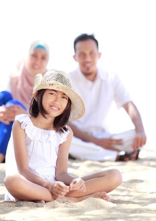 scarf beach: Retrato de ni�a peque�a en la playa sonr�e con su padre como fondo Foto de archivo