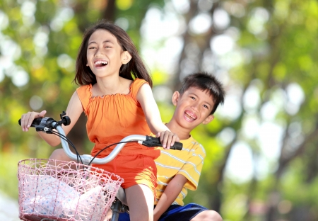happy asian family: happy smiling kids enjoy riding bicycle together outdoor