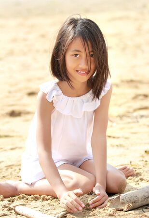 portrait of young little girl sitting in the beach smiling photo