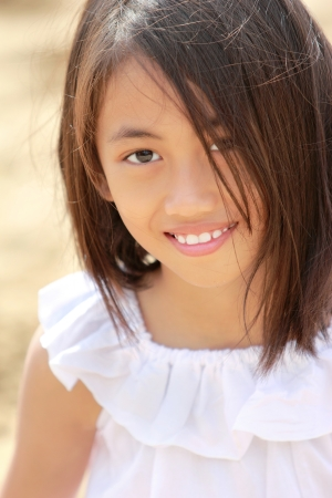 breeze: portrait of young little girl sitting in the beach smiling Stock Photo