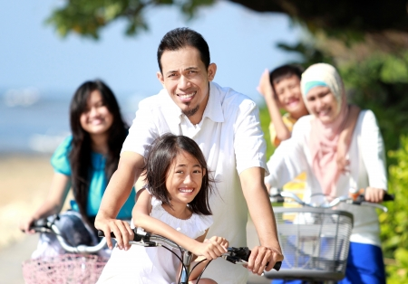 mujeres musulmanas: Familia feliz asi�tica andar en bicicleta por la ma�ana hermosa en la playa