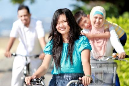familias unidas: Familia feliz asiática andar en bicicleta por la mañana hermosa en la playa