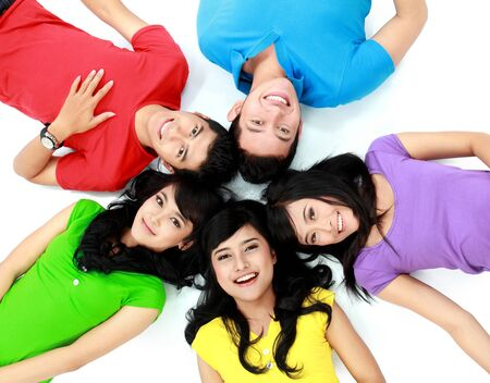 lying down: happy group of friends smiling with their heads together on the floor