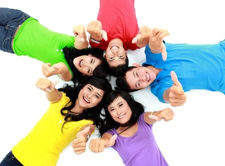 Šťastné skupina přátel si lehl na podlahu ukazuje palec nahoru