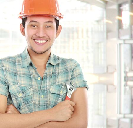 Portrait of an happy worker at construction building holding a wrench photo
