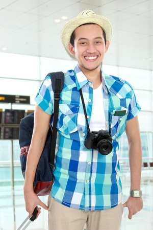smiling tourist carrying bag and camera in the airport photo