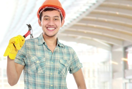 contruction: Portrait of an happy worker with hammer at contruction sites Stock Photo