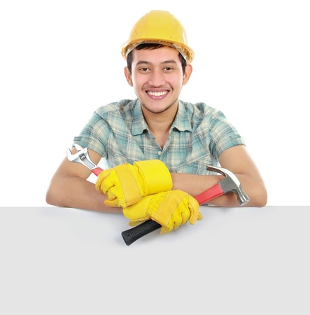 Construction worker leaning over blank white space Isolated on white background photo