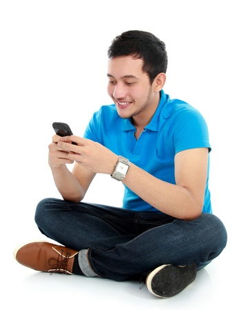 young asian man texting message at his mobile phone photo