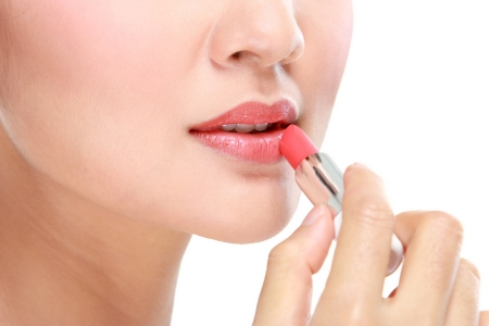 mujer maquillandose: cerca de los labios con el lápiz labial aislado sobre fondo blanco