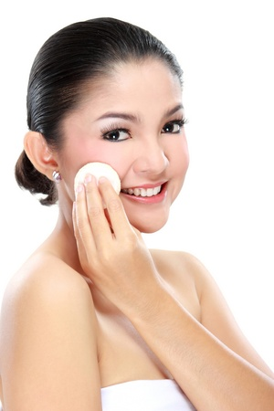 beautiful young adult woman with cotton pad. applying face powder photo