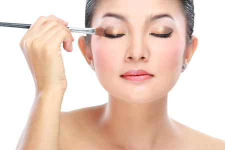 mujer maquillandose: Mujer joven hermosa con un cepillo del maquillaje. Aislado sobre fondo blanco Foto de archivo