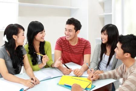 discutere: Gruppo di studenti che studiano e discutere insieme in una classe