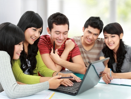 discussion group: Group of students using laptop together in a classroom Stock Photo