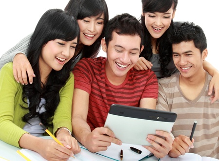 Group of students looking at tablet PC together on white background photo