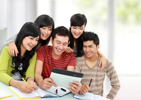 Group of happy students using tablet computer together photo