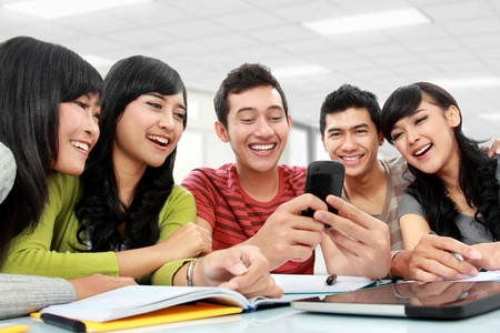 Group of students using mobile phone together photo