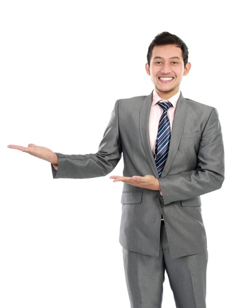 blank area: Happy smiling young business man showing blank area for sign or copyspase