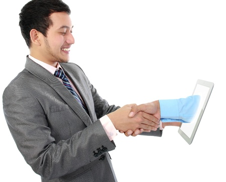 online deal concept. business man shake hand with client throught tablet pc photo