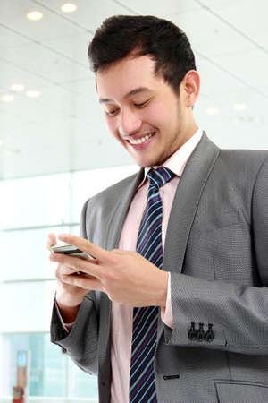 Young business man texting a message with phone in the office photo