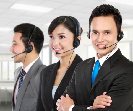 call center office: Smiling operator doing her job with a headset in the office Stock Photo