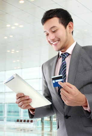 potrait of young businessman with tab and credit card doing online shopping
