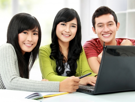 Group of young student smiling using laptop photo