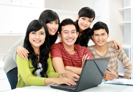 Group of young student  using laptop together photo