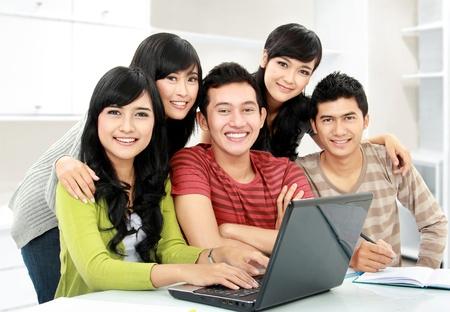 laptop asian: Grupo de joven estudiante utilizando equipo port�til en conjunto