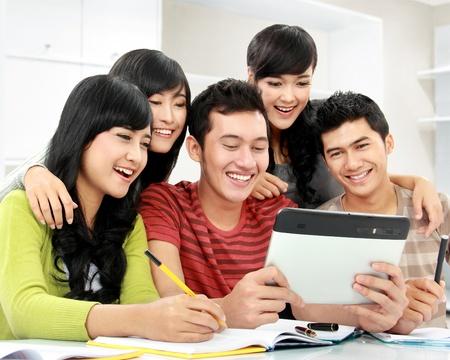 discutere: Gruppo di studenti, cercando in tablet pc insieme Archivio Fotografico