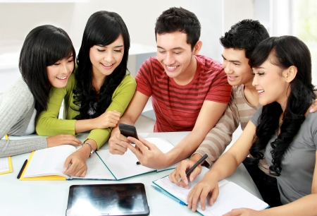 discuss: Group of asian students looking at handphone together