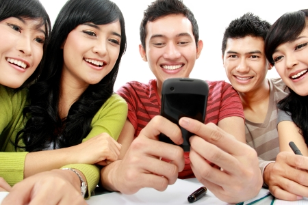 handphone: Group of students smiling looking at cellphone together