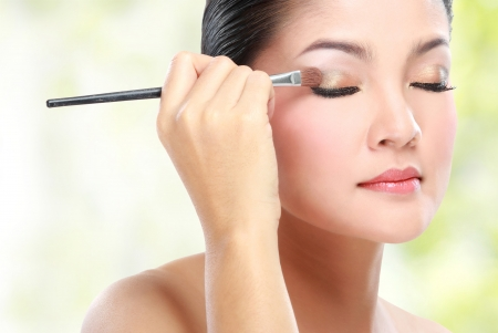maquillaje de ojos: Hermosa mujer joven de aplicar el maquillaje de párpados con maquillaje cepillo aislado en el fondo blanco