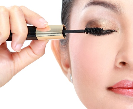 Beautiful woman applying mascara on her eyelashes isolated on white background