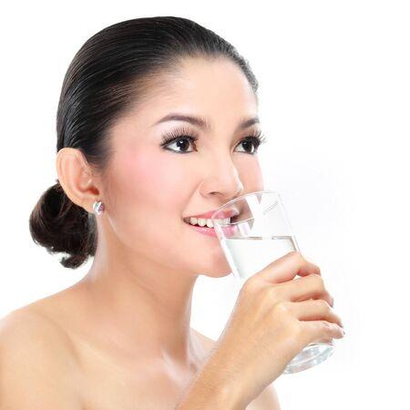 vaso de agua: Retrato de una mujer hermosa joven que bebe un vaso de agua aisladas sobre fondo blanco