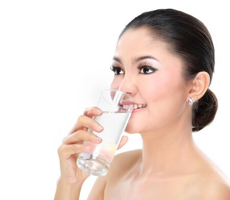 Portrait of a beautiful young woman drinking a glass of water isolated on white background photo