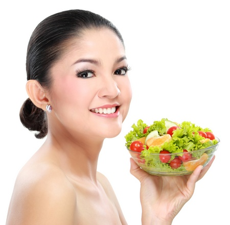 Closeup portrait of an beautiful young woman with salad photo