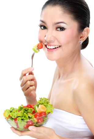 Closeup portrait of an attractive young woman eating vegetable salad photo