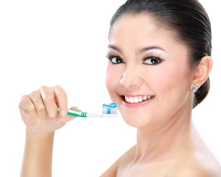 Beautiful woman brushing her teeth isolated on white background photo