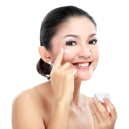 Beautiful women applying moisturizer cosmetic cream on face photo