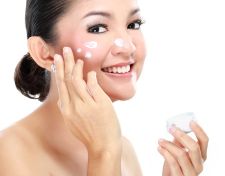 face cream: Beautiful women applying moisturizer cosmetic cream on face